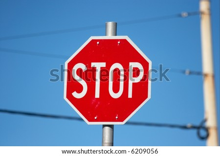 Red stop sign under clear blue sky, wires in the background, urban environment