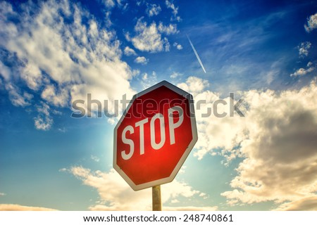 red stop sign with blue sky and clouds and airplane contrail - stock photo
