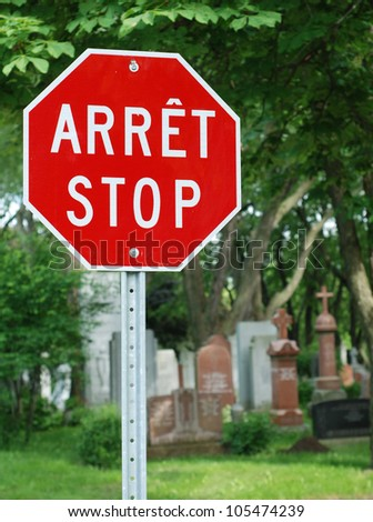 Red stop sign with French 'Arret' and English 'Stop' - stock photo