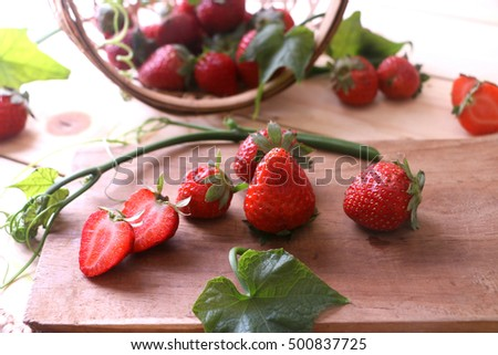 Red strawberries on a chopping board.