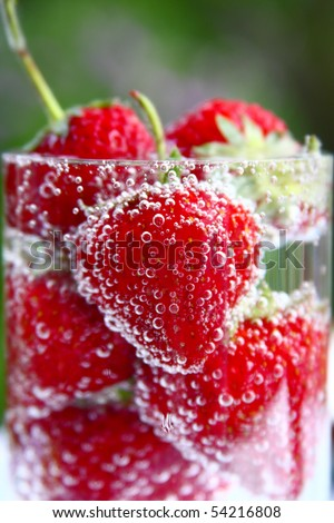 Red strawberry in water covered with vials - stock photo