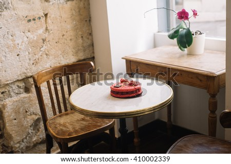 Red strawberry macaroon cake with raspberry and pistachio alone on a table in Parisian cafe - stock photo