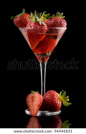 red strawberry on dark background with glass - stock photo