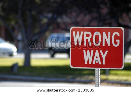 Red street sign stating wrong way direction - stock photo