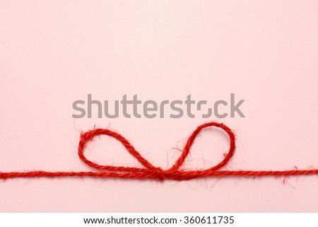 Red string bow on a pink paper background. - stock photo
