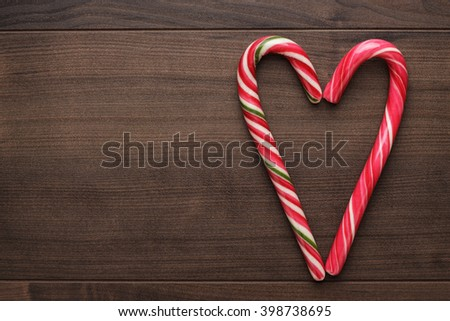 red sugar lollipops form heartshape on the wooden table - stock photo