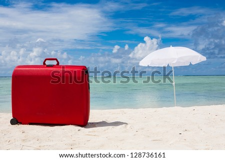 red suitcase and white sunshade at the beach - stock photo