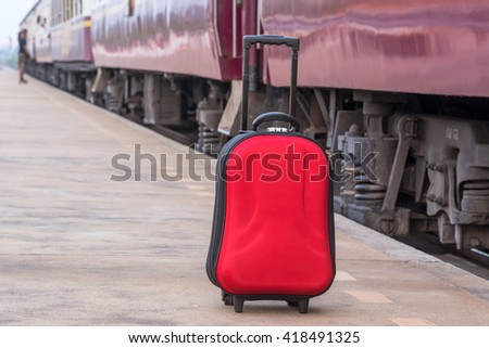red suitcase at train station, focus at suit case - stock photo