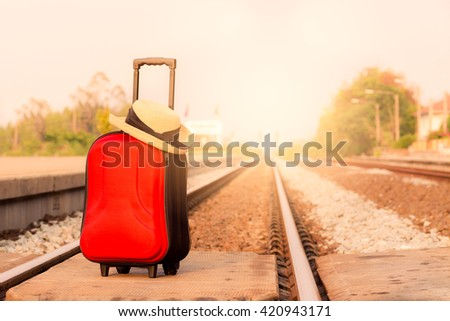 red suitcase at train station with abstract light, focus at suit case - stock photo