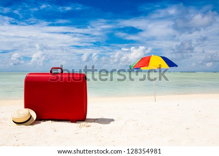 red suitcase, straw sun hat and colorful sunshade at a beach with a blue ky and some clouds - stock photo