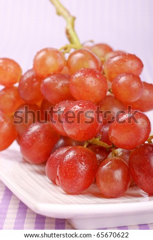 Red Sultana grape on a white plate. Studio shot. Selective focus, shallow DOF. - stock photo