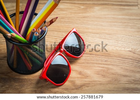 Red sun glasses with bunch of color pencils in a stand - stock photo