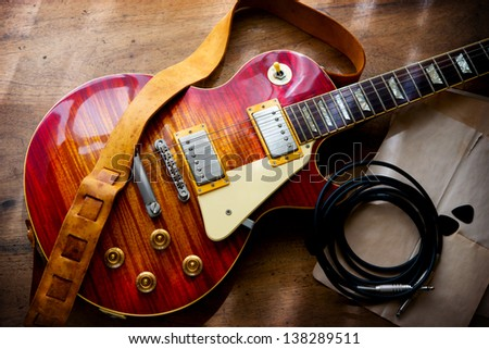 Red sunburst solid body electric guitar, in backstage or studio style setting. - stock photo