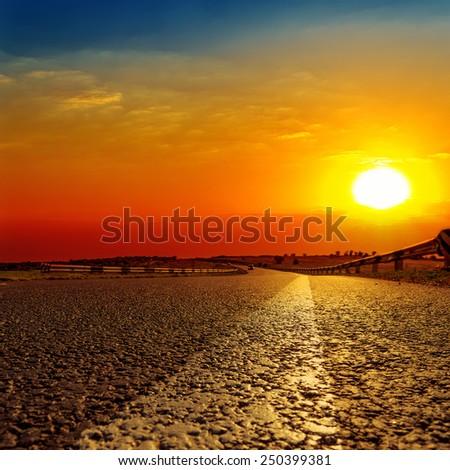 red sunset over asphalt road - stock photo