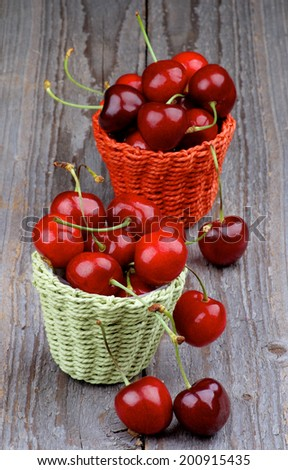 Red Sweet Cherries in Wicker Baskets closeup on Rustic Wooden background - stock photo