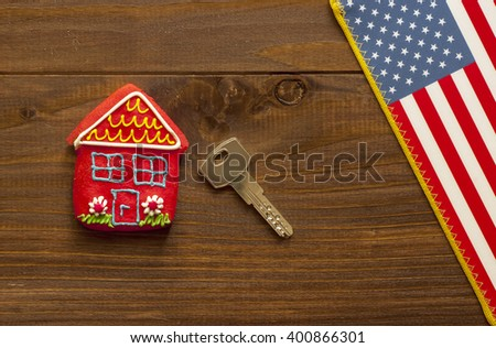 Red sweet  house , key and american flag on wooden background