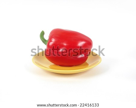 red sweet pepper rests upon yellow saucer