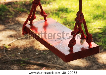 Red swing under a shade tree - stock photo