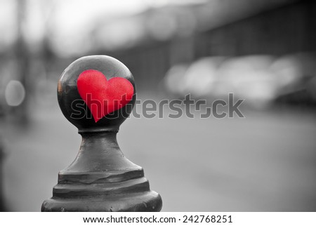Red symbolic heart close up. Industrial black and white cityscape in background. - stock photo