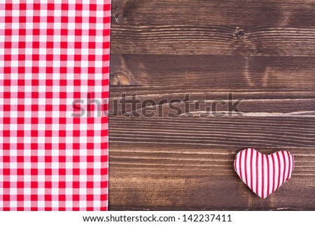 Red tablecloth, heart on old wooden background - stock photo