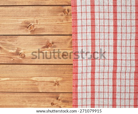 Red tablecloth or towel over the surface of a brown wooden table - stock photo