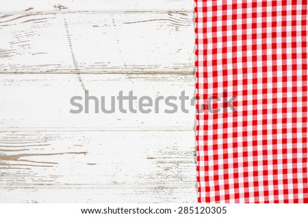 Red tablecloth over wooden table - stock photo