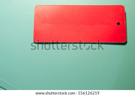 Red tag on a green background.