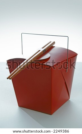 Red takeout container with chinese chopsticks - stock photo