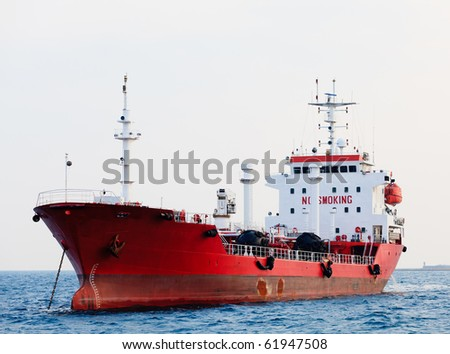 Red tanker is at anchor near the port. - stock photo