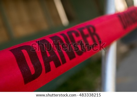 Red tape with Danger warning shot close up, background out of focus
