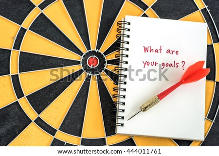 Red target arrow on open notebook with alphabet letters hand writing word what are you goal and question mark over dartboard background, Marketing concept - stock photo