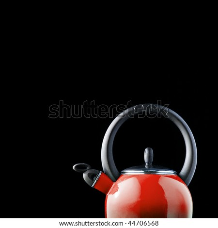 Red teapot on black background