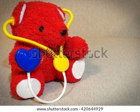 Red teddy bear with stethoscope - stock photo
