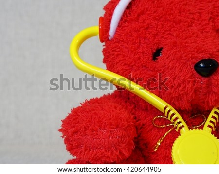 Red teddy bear with stethoscope. Free text space on left. - stock photo