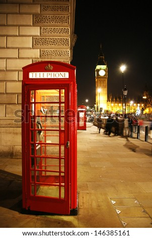 Red Telephone Booth at night, Big Ben in the distance. Red phone booth is one of the most famous London icons.  - stock photo