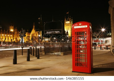Red Telephone Booth at night, Victoria Tower in the distance. Red phone booth is one of the most famous London icons.  - stock photo