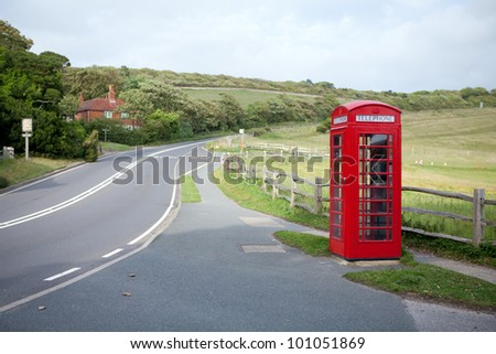 Red telephone booth beside the road on the hills - stock photo