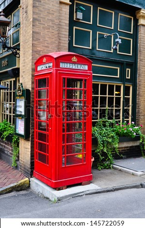 red telephone booth next to a pub - stock photo