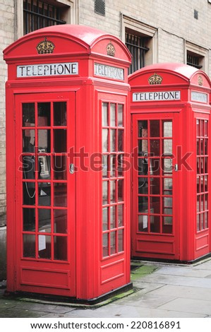 Red telephone booths in a street in London - stock photo