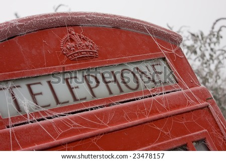 Red telephone box in cold - stock photo