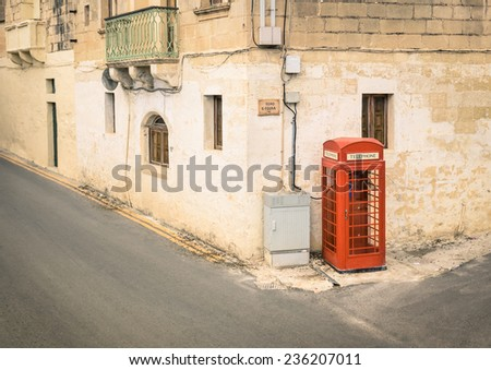 Red telephone cabin in the medieval old town of Victoria in Gozo - Mediterranean archipelago of Malta - stock photo