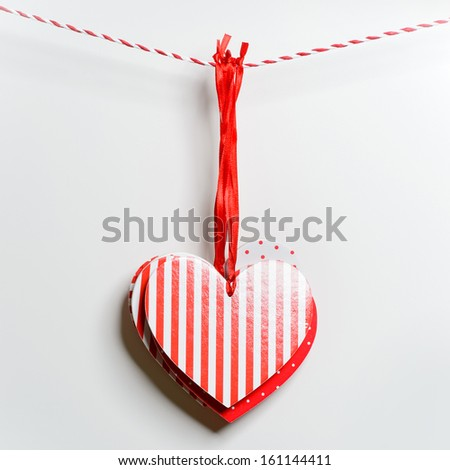 Red textured hearts hanging on white background - stock photo