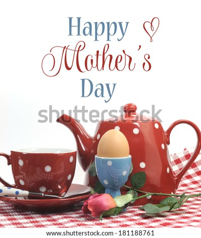 Red theme Happy Mothers Day breakfast in bed with tea cup, tea pot and egg in red and blue polka dot china with sample text or copy space. - stock photo