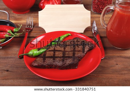red theme lunch fresh grilled bbq roast beef steak red plate green chili tomato soup ketchup sauce paprika glass ground pepper american peppercorn modern cutlery served wooden table empty nameplate - stock photo