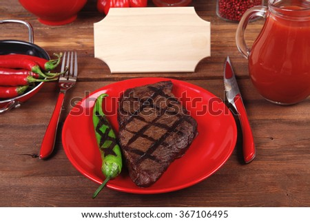 red theme lunch : fresh grilled bbq roast beef steak red plate green tomato soup ketchup sauce paprika small glass ground pepper american peppercorn modern cutlery served wooden table empty nameplate - stock photo
