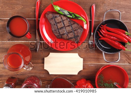 red theme lunch : fresh grilled bbq roast beef steak red plate tomato soup ketchup sauce paprika jug glass ground pepper american peppercorn modern cutlery served on wooden table with empty nameplate - stock photo
