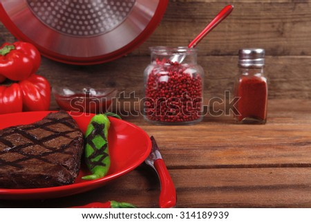 red theme lunch : fresh grilled bbq roast beef steak red plate with green chili tomato soup ketchup sauce paprika small jug glass ground pepper american peppercorn modern cutlery served wooden table - stock photo