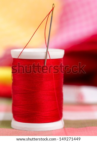 Red thread reel with colorful out of focus clothes on the background - stock photo