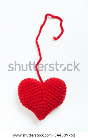 Red thread to the crochet heart, isolated on white background. Valentine's Day. Symbol of love.