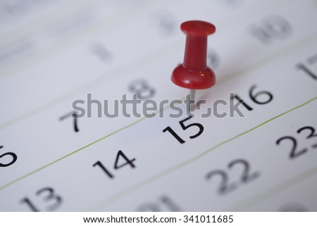 Red Thumb Tack on Calendar Page - stock photo